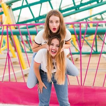 Amigas felices divirtiéndose en el parque de atracciones