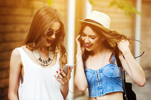 Amigas felices mirando la pantalla del teléfono al atardecer