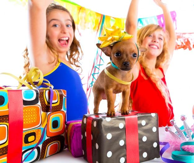 Amigas fiesta bailando con regalos y cachorro