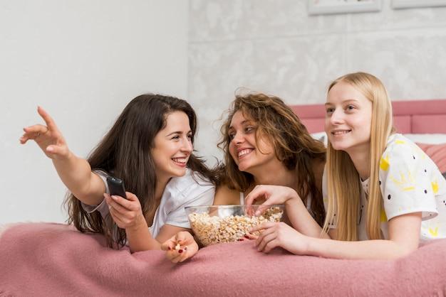 Amigas en fiesta de pijamas comiendo palomitas