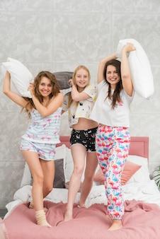 Amigas en fiesta de pijamas peleando con almohadas