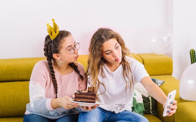 Amigas haciéndose un selfie con trozo de tarta