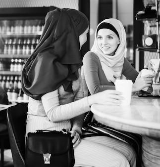 Amigas islámicas disfrutando y hablando en la cafetería.