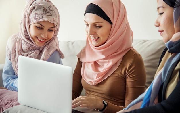 Amigas islámicas sentadas en el sofá hablando y usando una computadora portátil