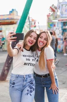 Amigas jóvenes haciendo un selfie en el parque de atracciones