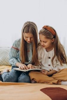 Amigas leyendo un libro juntos en casa
