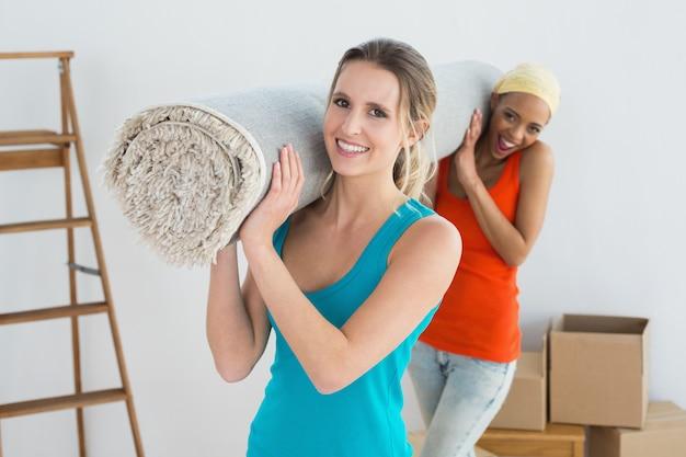 Amigas llevando alfombra enrollada después de mudarse a una casa