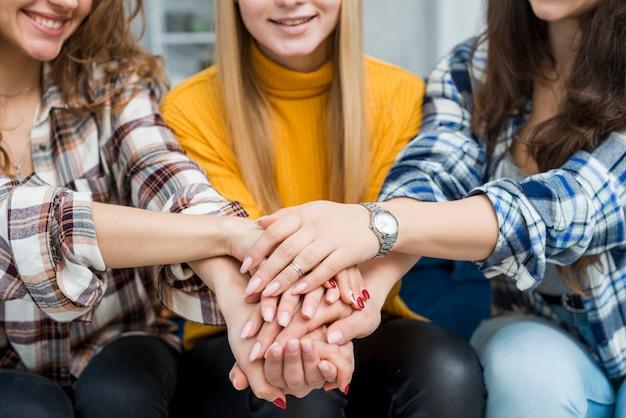 Amigas con las manos juntas