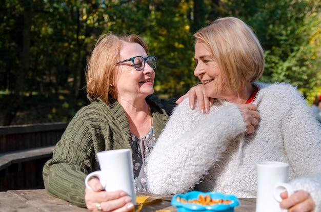 Las amigas mayores disfrutan de una bebida caliente sentados en la terraza. los mayores beben té. retrato en la cintura