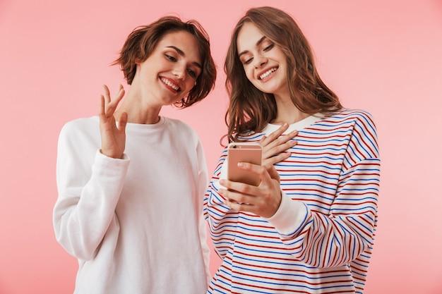 Amigas de mujeres aisladas sobre pared rosa mediante teléfono móvil.