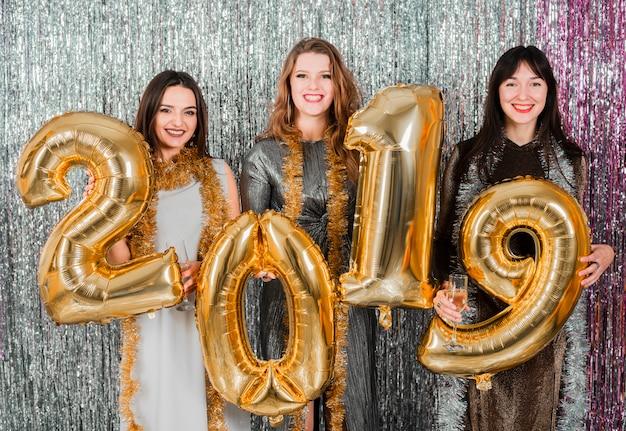 Amigas posando con globos dorados en fiesta de año nuevo