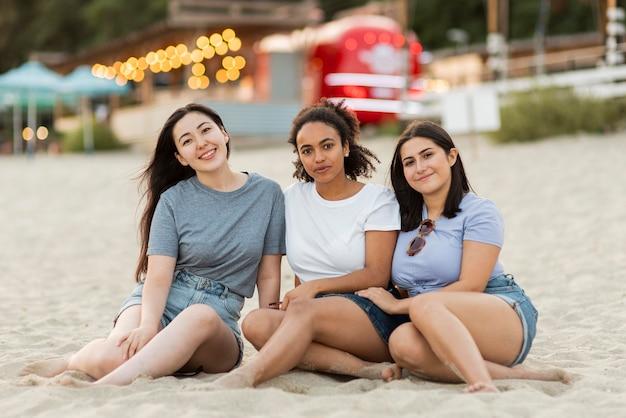 Amigas posando juntos en la playa