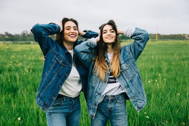 Amigas posando y sonriendo en el campo