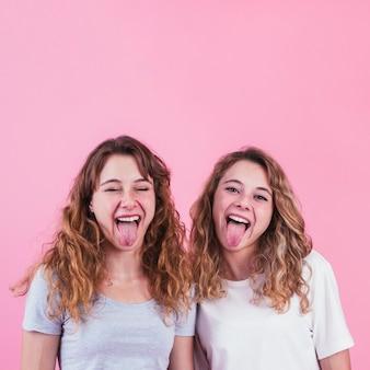 Amigas sacando la lengua de pie contra el fondo rosa