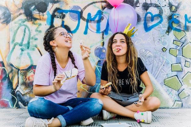 Amigas sentadas con globos y hojaldre de cumpleaños
