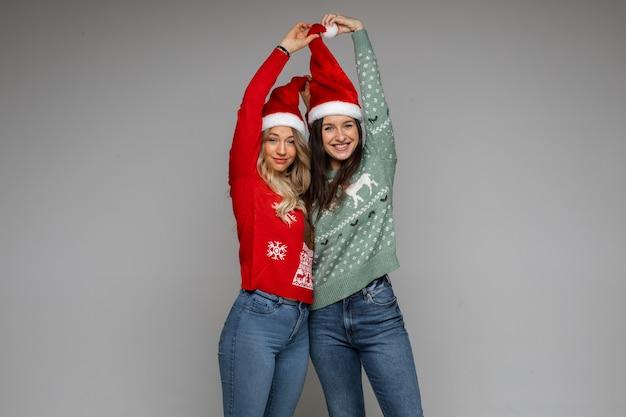 Amigas con sombreros de navidad rojos y blancos