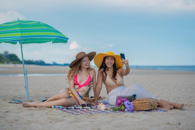 Amigas sonrientes sentadas en la colchoneta y usando un sombrero tomando una fotografía selfie con un teléfono inteligente juntos