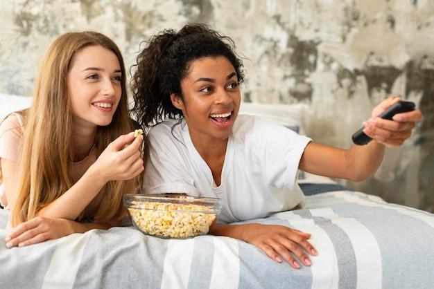 Amigas sonrientes viendo la televisión en la cama