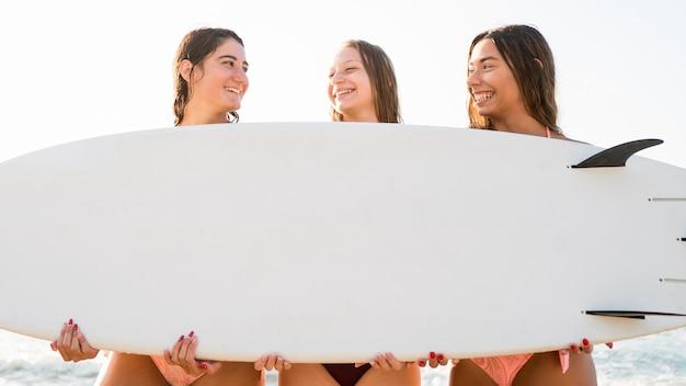Amigas de tiro medio sosteniendo la tabla de surf