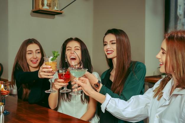 Amigas tomando una copa en el bar. están sentados en una mesa de madera con cócteles. están tintineando vasos