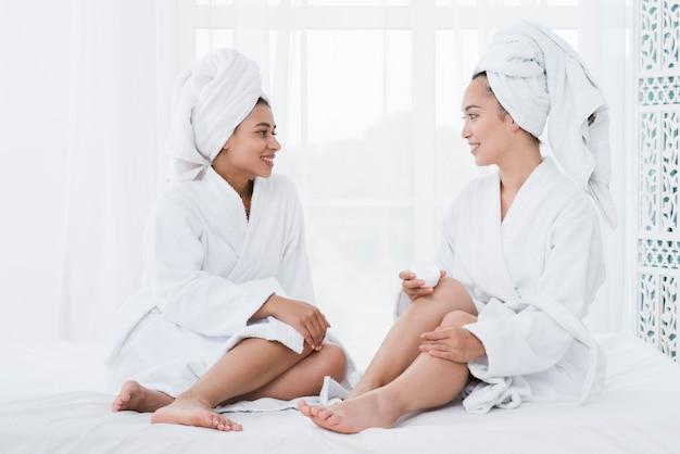 Amigas usando crema de belleza en un spa