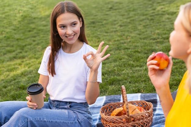 Amigas usando lenguaje de señas al aire libre