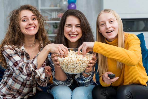 Amigas viendo una película mientras comen palomitas