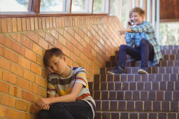 Amigo de la escuela intimidando a un niño triste en el pasillo de la escuela