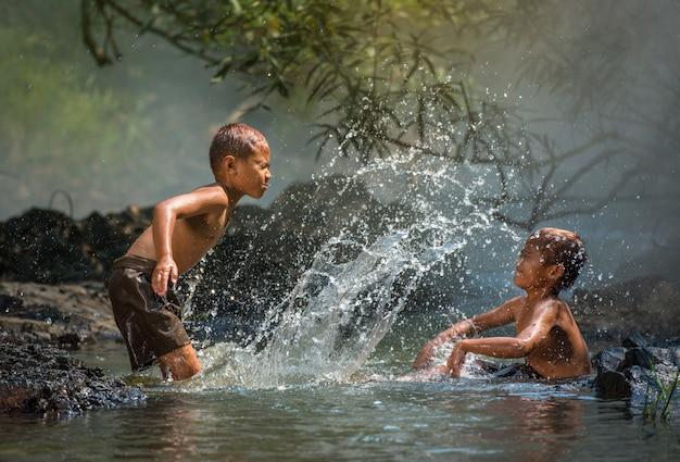 El amigo feliz divertido jugando agua en la corriente de agua en el campo