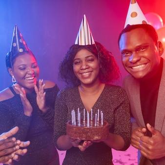 Amigo de vista frontal y pastel de feliz cumpleaños
