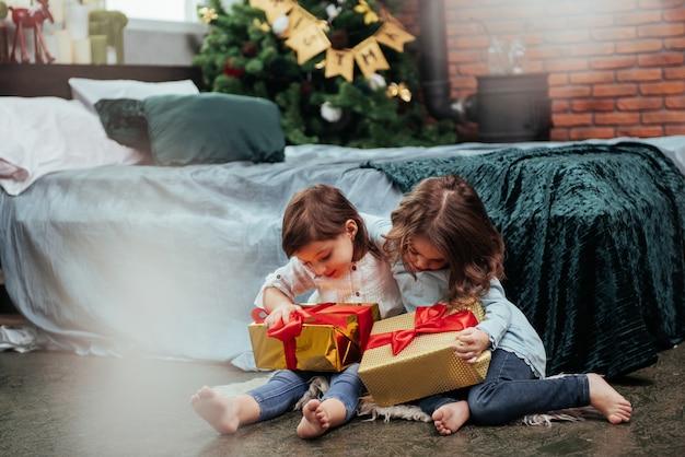 Los amigos se abrazan. vacaciones de navidad con regalos para estos dos niños que se sientan en el interior en la bonita habitación cerca de la cama