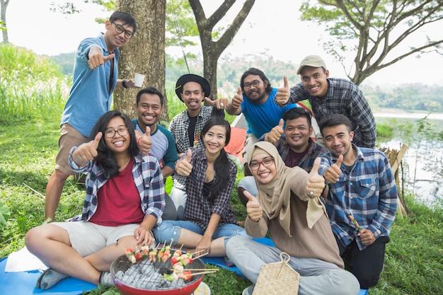 Amigos acampando mostrando el pulgar hacia arriba