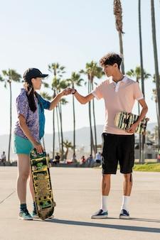Amigos adolescentes chocan el puño, patinadores en venice beach, los ángeles