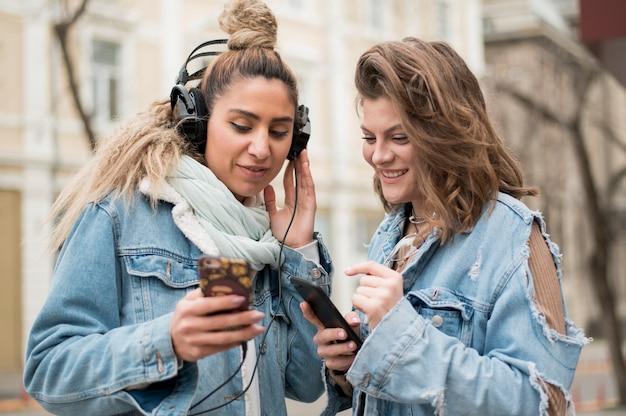 Amigos adolescentes compartiendo canciones al aire libre