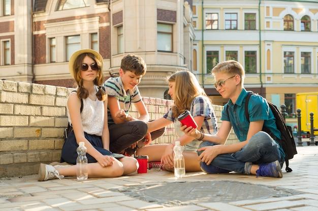 Los amigos adolescentes se divierten, hablan, leen el teléfono, el libro