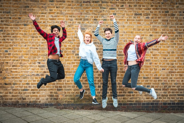 Amigos adolescentes felices saltando delante de una pared