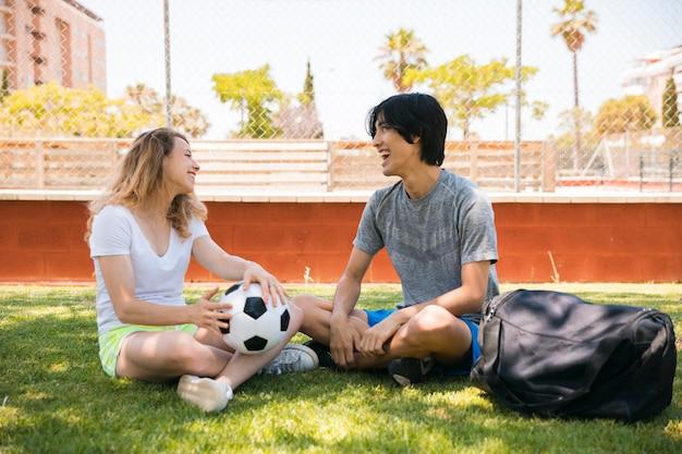 Amigos adolescentes multiétnicos que se sientan en el campo de fútbol
