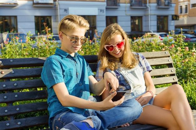 Amigos adolescentes niña y niño sentado en el banco en la ciudad