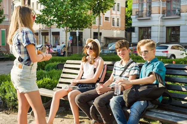 Amigos adolescentes niña y niño sentados en el banco de la ciudad