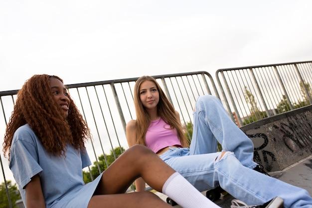 Amigos adolescentes pasar tiempo juntos al aire libre en la pista de patinaje