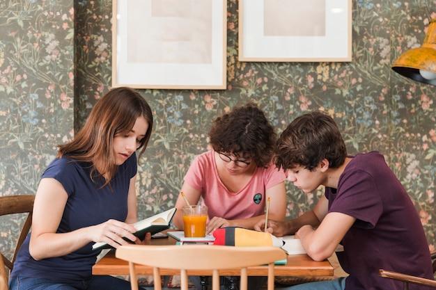 Amigos adolescentes que estudian en café