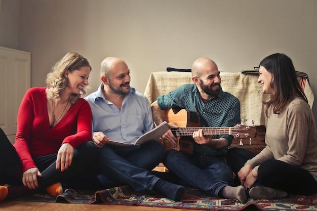 Amigos adultos sentados en una alfombra y disfrutando de un juego de guitarra
