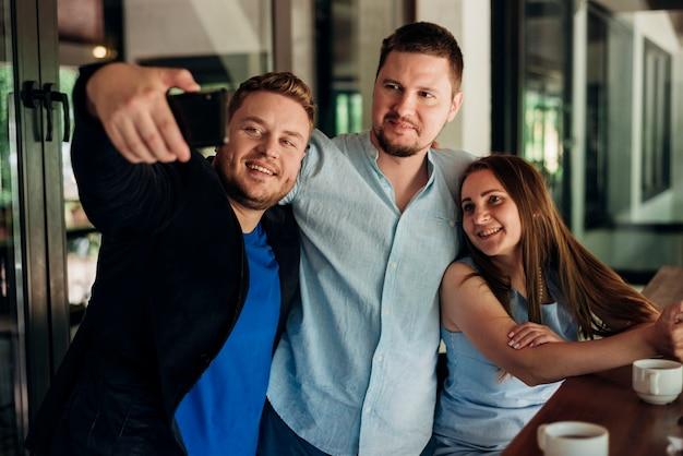 Amigos adultos tomando selfie en comedor