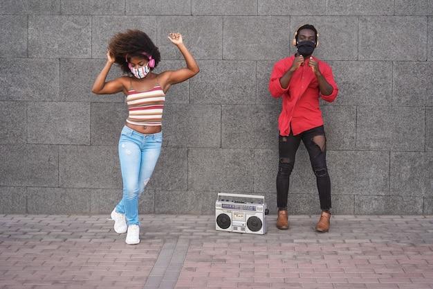 Amigos africanos bailando al aire libre escuchando música mientras usan máscaras de seguridad - centrarse en las caras