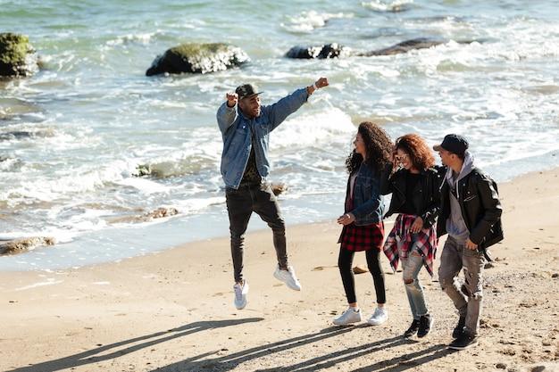 Amigos africanos felices caminando al aire libre en la playa