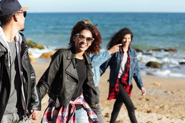 Amigos africanos sonrientes caminando al aire libre en la playa.