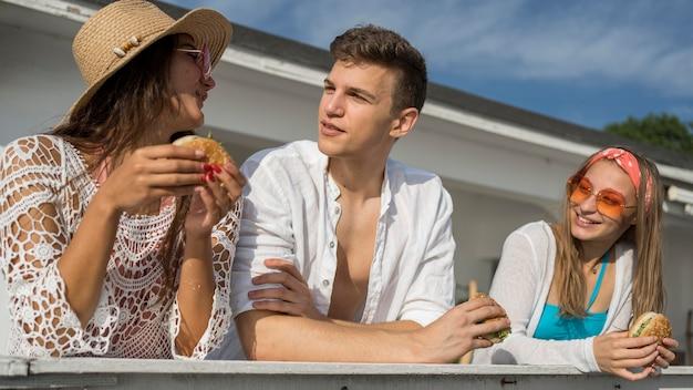 Amigos al aire libre disfrutando de hamburguesas juntos