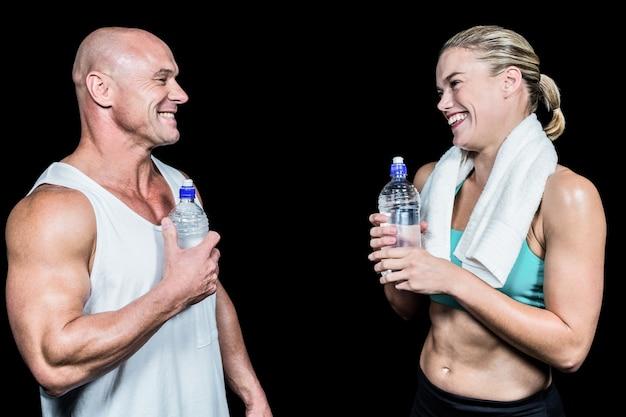 Amigos alegres del atleta con la botella de agua