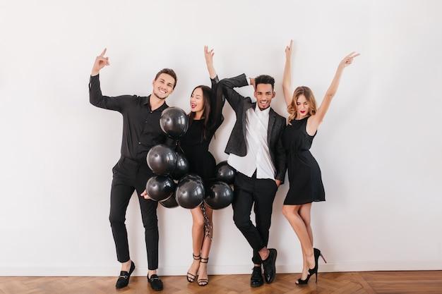 Amigos alegres bailando en la pared blanca con globos negros durante la fiesta en casa
