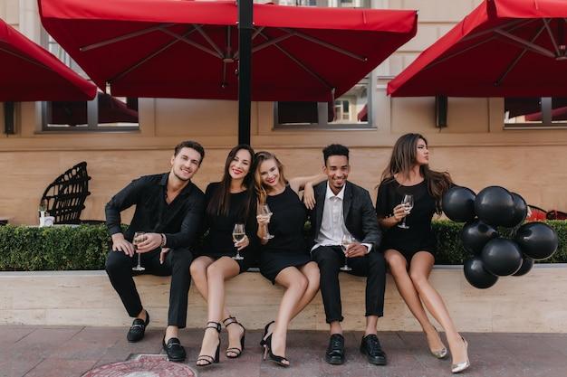 Amigos alegres bebiendo champán en la fiesta al aire libre